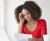 A woman reads the bad news that her job offer was rescinded.