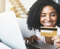 Woman using debit card to shop online