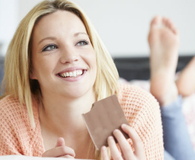 Woman eating bar of chocolate to make herself happier