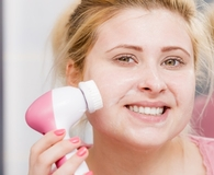 Woman using best facial cleansing devices