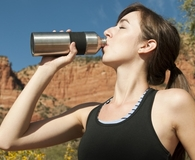 Woman drinking water out of stainless steel water bottle