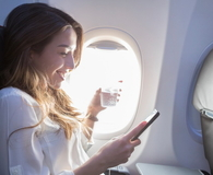 Woman enjoys in flight beverage and Wi-Fi
