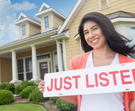 Woman holding 'just listed' sign in front of beautiful home