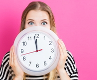 Woman holding clock showing nearly twelve