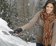 Woman using best windshield de-icers during winter