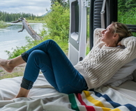 Woman laying in back of her Camping Van