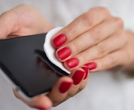 Woman using best electronic wipes to clean phone