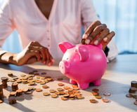 Woman putting money in a piggy bank