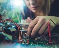 Woman repairing electrical component of a computer