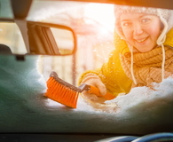 Woman scraping and cleans snow off car