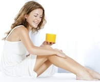 Woman applying best self-tanner on her legs