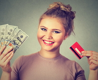 Woman shopping holding credit card cash dollar bills