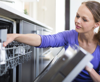 Woman loading smelly dishwasher and learning how to fix it