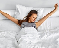 Woman waking up on memory foam mattress topper