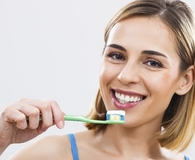 Woman using best manual toothbrush to clean her teeth