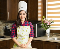 Woman with a chef's hat in the kitchen