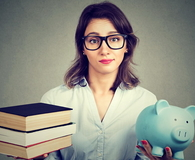 Woman with stack pile of books and piggy bank