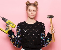 Young adult woman holding working tools in hands