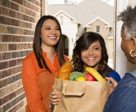 Young adults bring groceries to senior woman