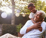 Young black boy embracing grandfather