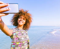 Young black woman taking a selfie at beach