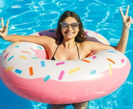 Young girl in doughnut float at pool