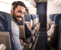 Young happy passenger flying in the airplane