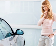 Young woman looking at car