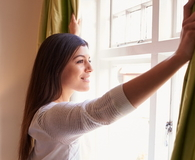 Young woman opens curtains to look at the view from