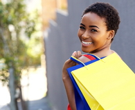 Young woman smiling with shopping bags outside