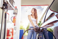 Pretty young woman refuel the car