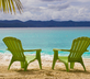 A pair of unoccopied green Adirondack chairs on the beach.