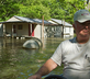 Man in front of flooded home